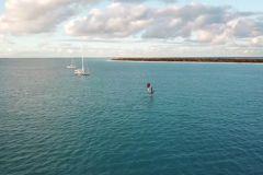 L'IMOCA Hugo Boss en course contre deux kitesurfers
