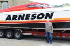 Howard Arneson devant un bateau de course offshore lors de ses 96 ans