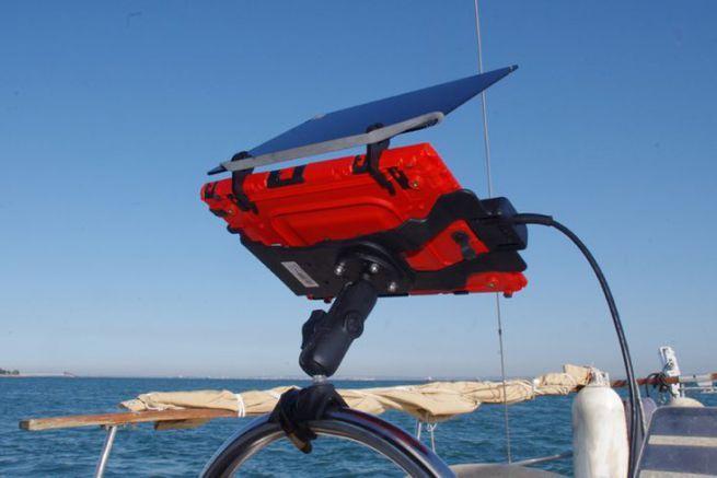 Une tablette dans sa protection avec le pare-soleil à la barre d'un voilier